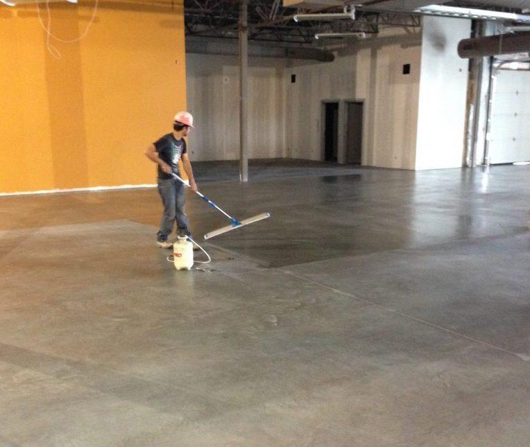 concrete coating calgary - worker applying floor coating